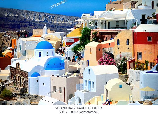 Hillside buildings with traditional church blue domes in Oia, Santorini, Greek Islands, Greece