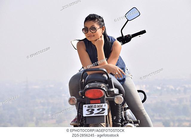 Young woman on bike near a mountain, Pune, Maharashtra