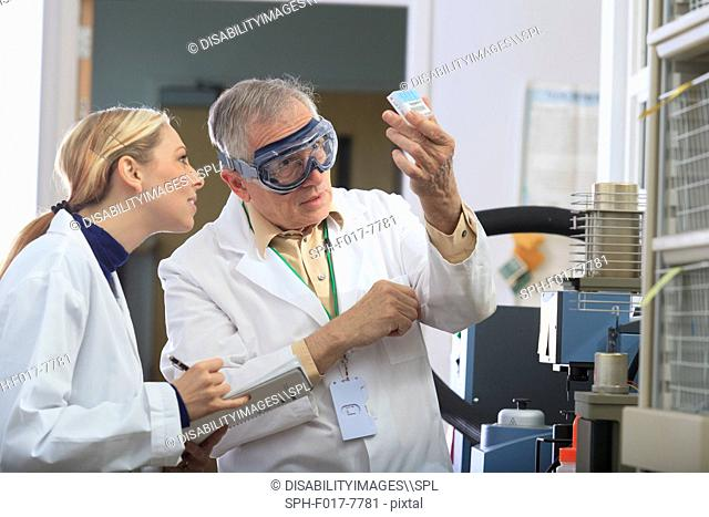Professor working with engineering student looking at reference samples for thermogravimetric analyser in a laboratory