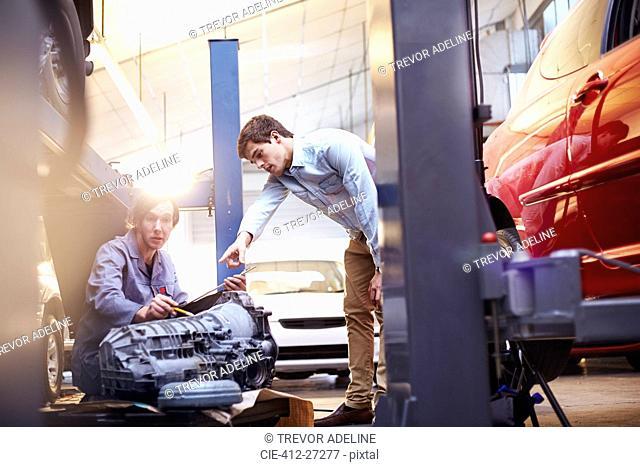 Mechanics discussing engine part in auto repair shop