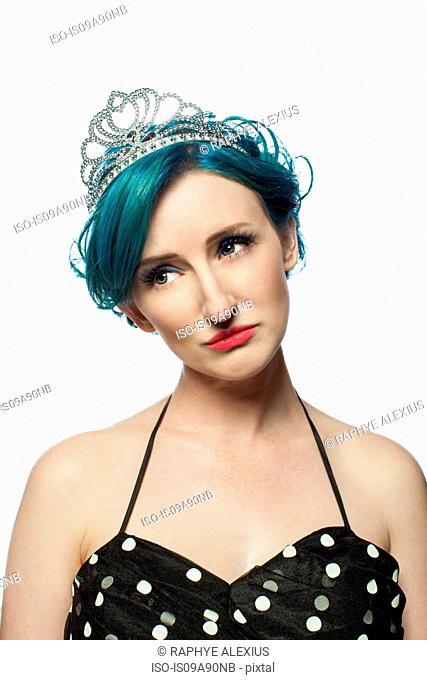 Young woman with green hair looking away against white background