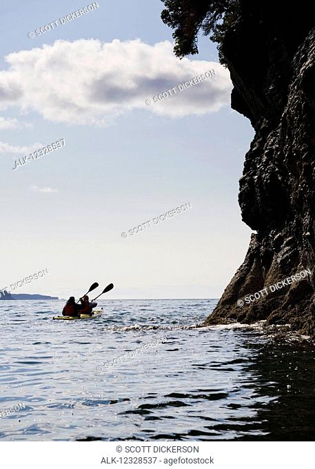 Two sea kayakers in a double sea kayak, Kachemak Bay, Southcentral Alaska; Alaska, United States of America