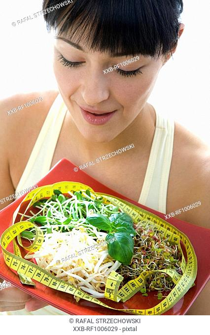 young woman with sprouts and measuring tape