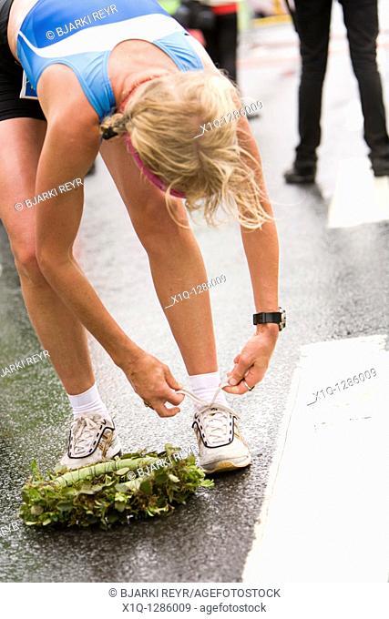 Martha Ernstdottir, winner, half-marathon, 2009 Reykjavik Marathon, Iceland  She is tying the laces on her shoes