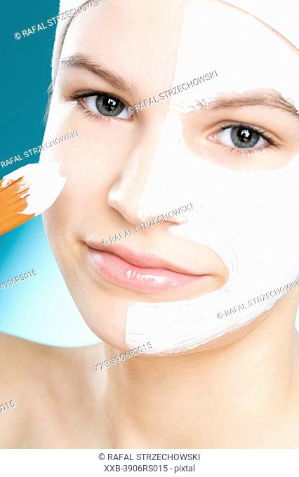 young woman with facial cream