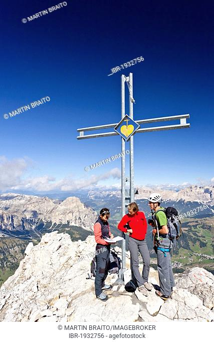 Mountaineers at the summit cross, Boeseekofel fixed rope route, Dolomites, Fanes group and Heiligkreuzkofel group at the back, province of Bolzano-Bozen, Italy