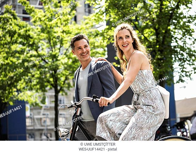 Happy couple with bicycle in the city