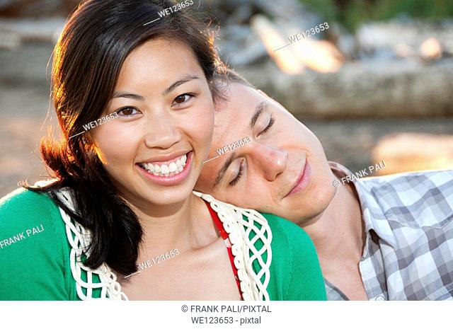 Young boy has his head on a chinese girls shoulder. She has a large smile