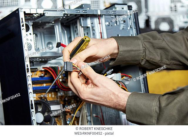 Worker in computer recycling plant dismantling desktop pc