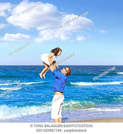 Family father holding daughter playing on the beach shore