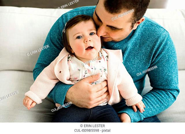 Baby girl looking up while being snuggled by her father