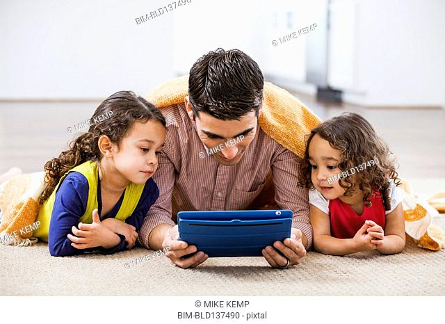 Father and daughters using tablet computer on living room floor