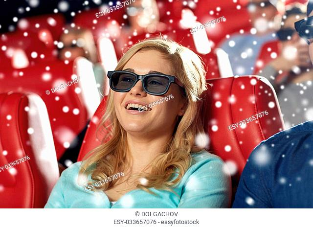 cinema, entertainment, technology and people concept - happy young woman in 3d glasses watching comedy and laughing in movie theater over snowflakes
