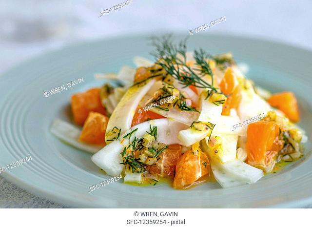 Salad of sliced fennel, shallot and clementine salad with a zingy dill dressing on a light jade coloured plate with vintage cutlery