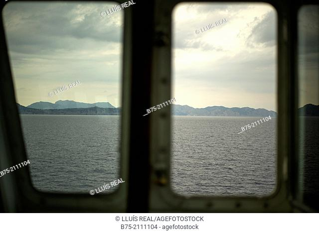 View of the sea, land and the sky through a window of a boat. Croosing the Mediterranean Sea from Ciutadella, Aberdeen to Alcudia, Mallorca, Balearic Islands