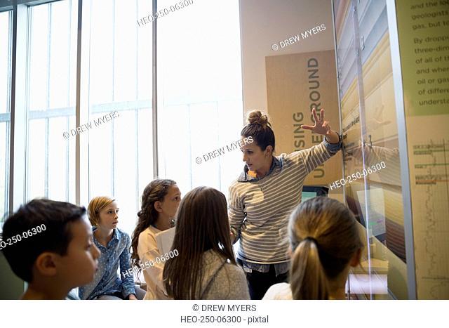 Teacher explaining exhibit to students in science center