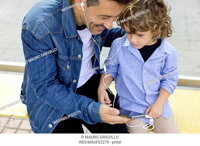 Father and son sitting at tram stop in the city sharing cell phone and earbuds