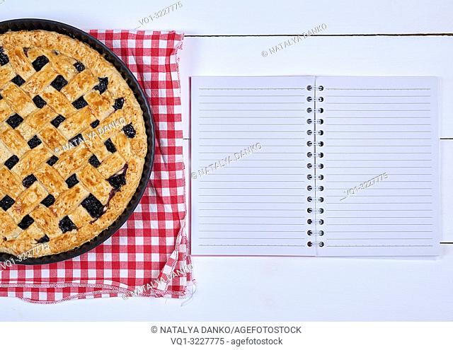round black currant pie and an open notebook with empty white sheets in line on a wooden background, top view