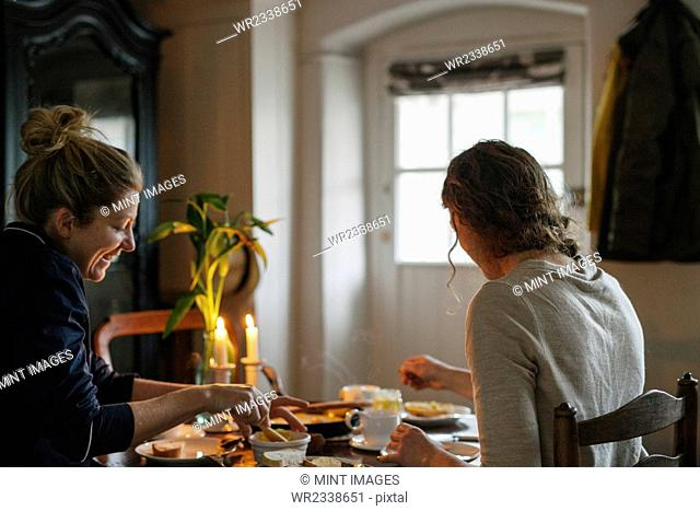 Two women sitting at a table having a meal by candlelight