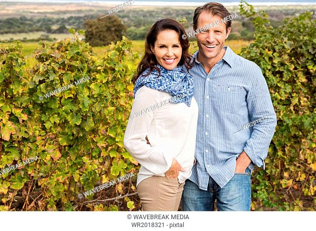 Cute couple posing in front of vineyard