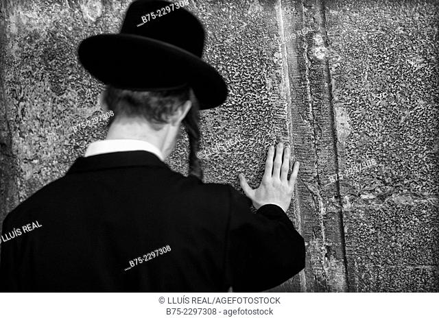 Unrecognizable jewish man seen from behind, praying in the synagogue in Wailing Wall Western Wall Plaza, Jewish Quarter, Jerusalem, Israel