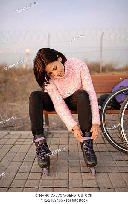 Young attractive woman puts rollerblades on at sunset