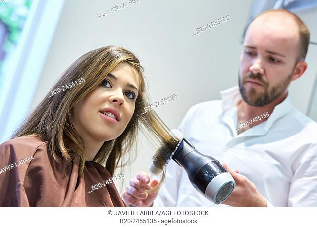 Hairdresser combing the hair of a woman. Hairdressing salon and Beauty Clinic