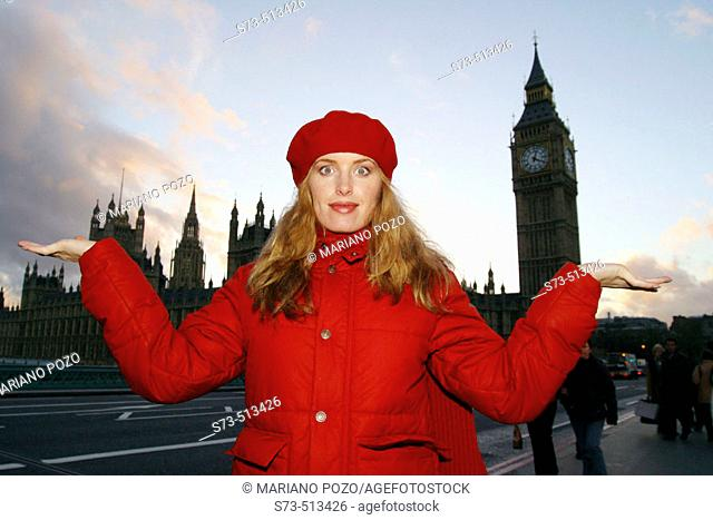 Red dressed young woman in front of Houses of Parliament, London. England, UK