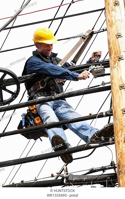 Communications worker attaching a combiner box to suspended cables