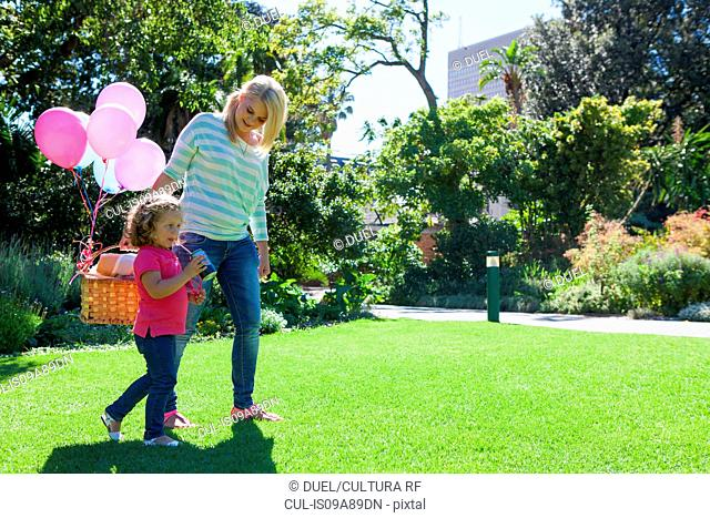 Mother and daughter walking in garden with basket of balloons