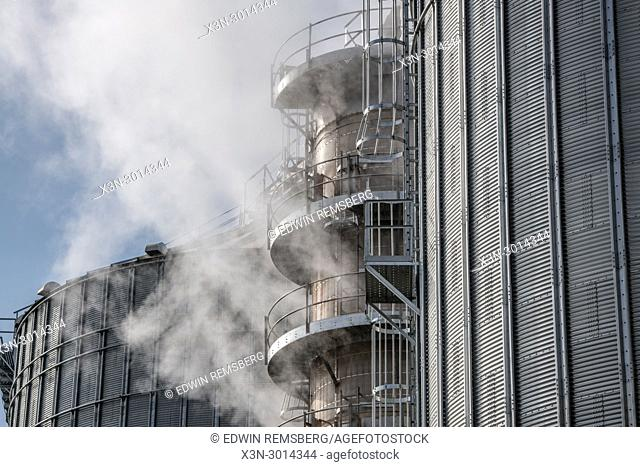 Steam bellowing out of grain drier next to silo storing soybeans, Pennsylvania. USA