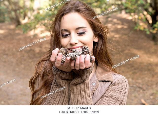 A young woman standing with a handful of pine cones in a forest in Autumn