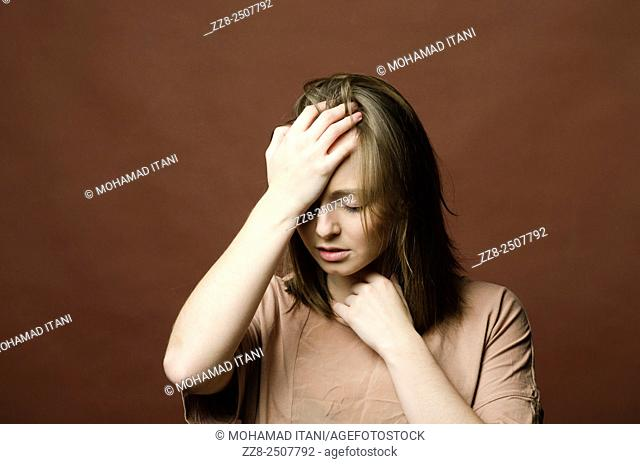 Depressed young woman hand on head