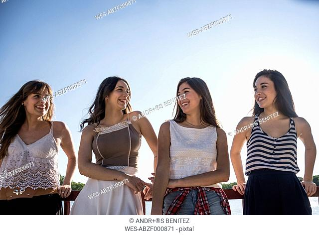 Four happy friends standing side by side at sunlight