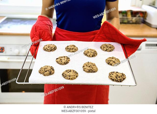 Woman showing a tray of freshly baked cookies