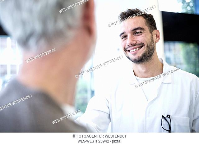 Man in doctor's overall smiling at grey-haired man