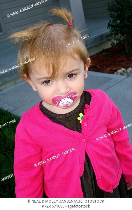 Shy young girl with a pacifier