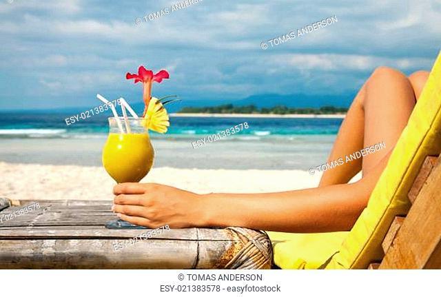 Holding a cocktail on a tropical beach