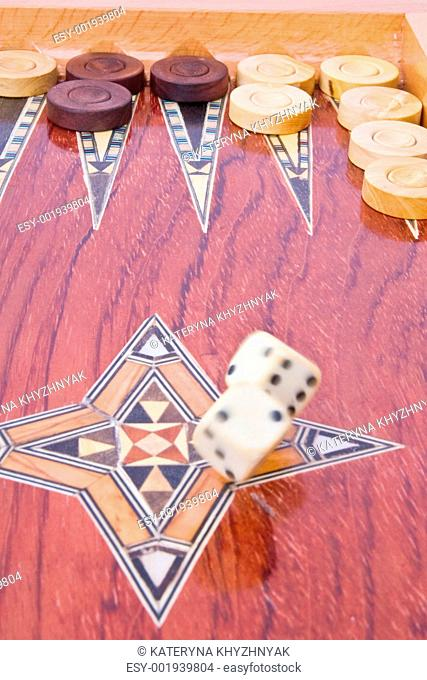 White big dices falling on wooden handmade backgammon board isol