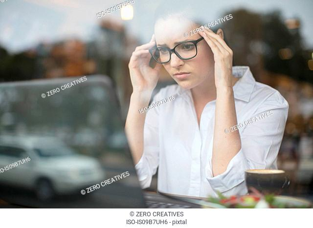 Woman using laptop looking stressed