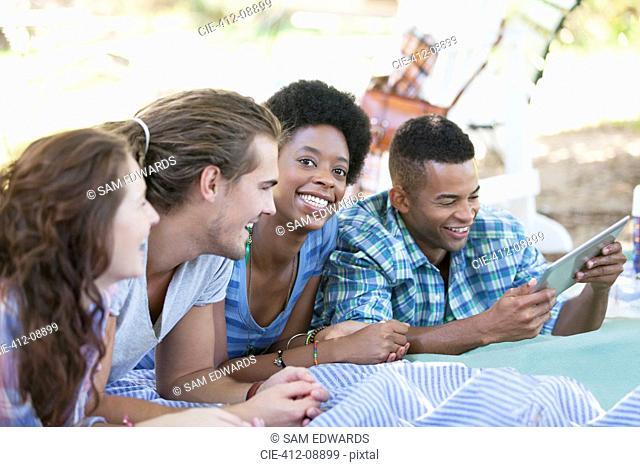Friends using digital tablet on blanket