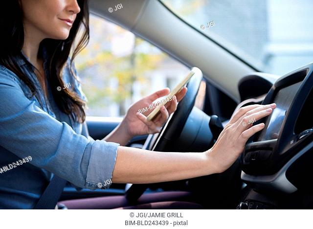 Caucasian woman in car holding cell phone programming journey