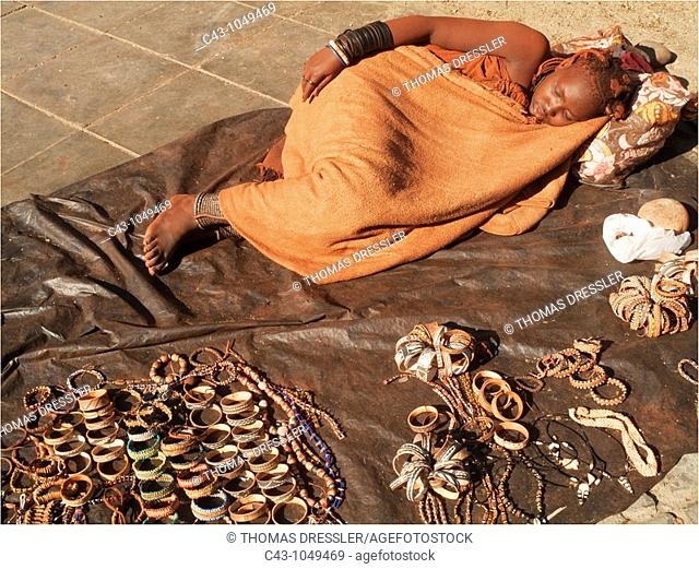 Namibia - The unusual sight of a Himba woman in the seaside town of Swakopmund sleeping next to the souvenirs displayed for sale  The Himba people live hundreds...