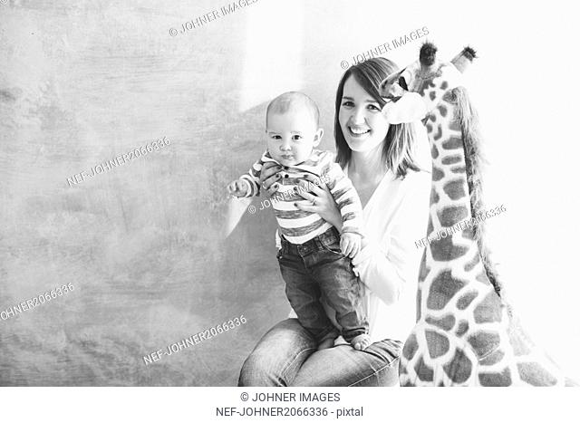 Mother holding baby boy next to toy giraffe