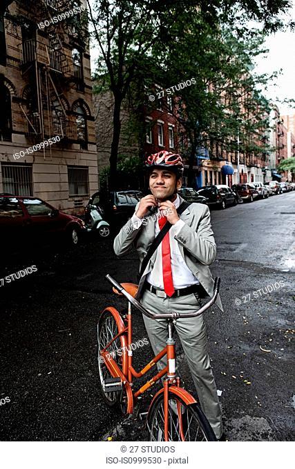 Young businessman adjusting cycle helmet in street