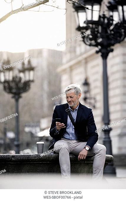 Grey-haired businessman in the city with smartphone and coffee to go