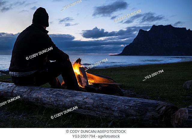 Man sits at evening campfire at Utakleiv beach, Lofoten Islands, Norway