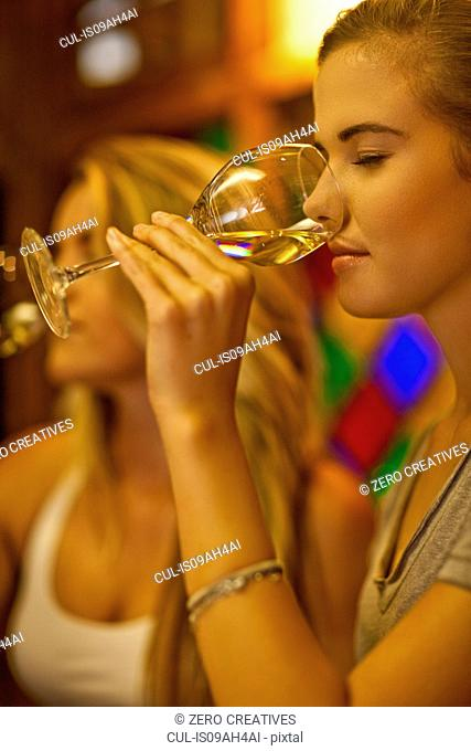 Two young women tasting white wine in wine bar