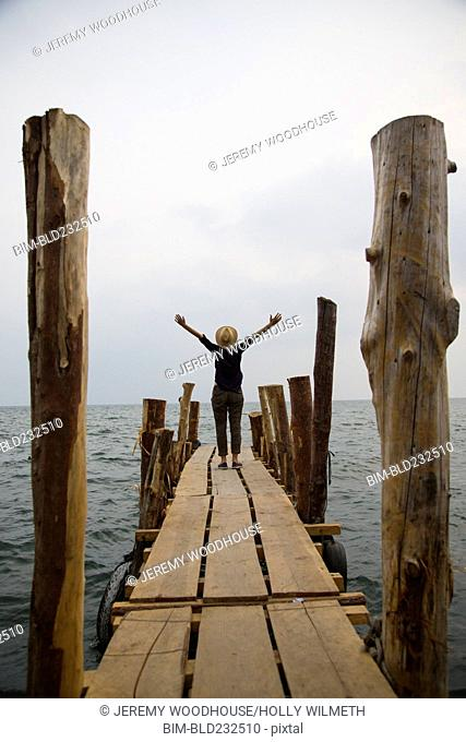 Woman standing on dock at lake with arms outstretched