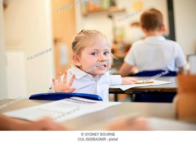 Mischievous schoolgirl in classroom lesson at primary school